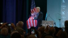 Donald Trump hugs American flag as he is applauded for anti-immigration speech