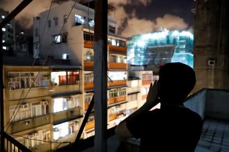 Choco Chu shouts slogan from his rooftop at Sham Shui Po in Hong Kong
