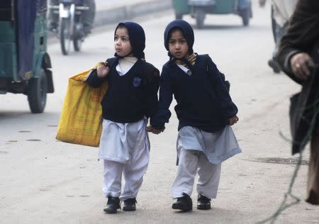 Girls carry their school bags as they walk along a road while heading to their school after it reopened in Peshawar