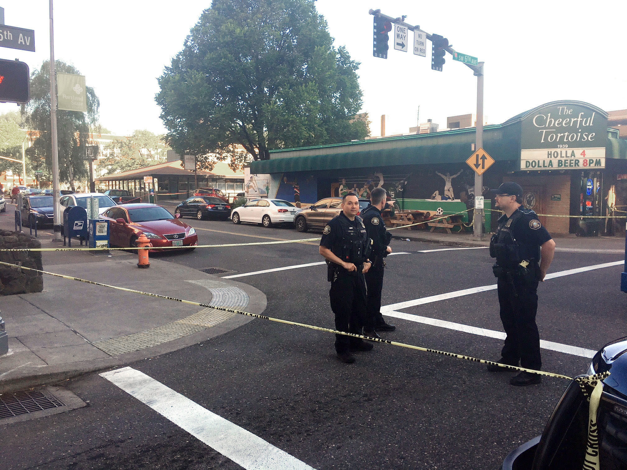 FILE - In this June 29, 2018, file photo, police stand outside across from The Cheerful Tortoise bar at the scene of an earlier shooting in Portland, Ore. Portland State University said Thursday, Aug. 13, 2020, it will disarm its campus police force more than two years after officers from the department shot and killed a Black man who was trying to break up a fight. (Shane Dixon/The Oregonian via AP, File)