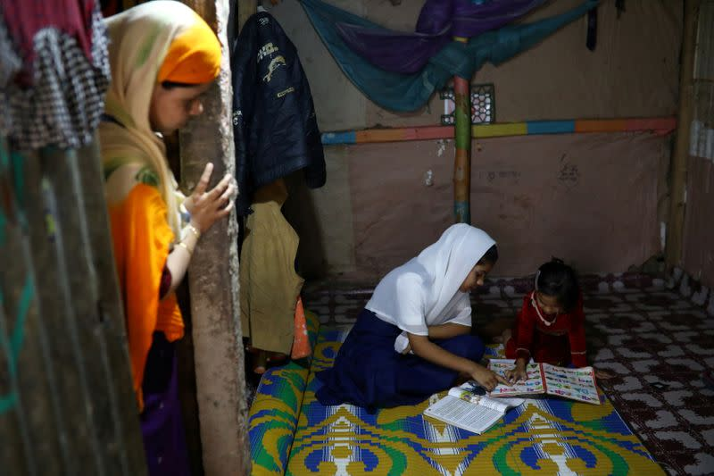 FILE PHOTO: Yasmin, a Rohingya girl who was expelled from Leda High School for being a Rohingya, helps her younger sister to study in Leda camp in Teknaf