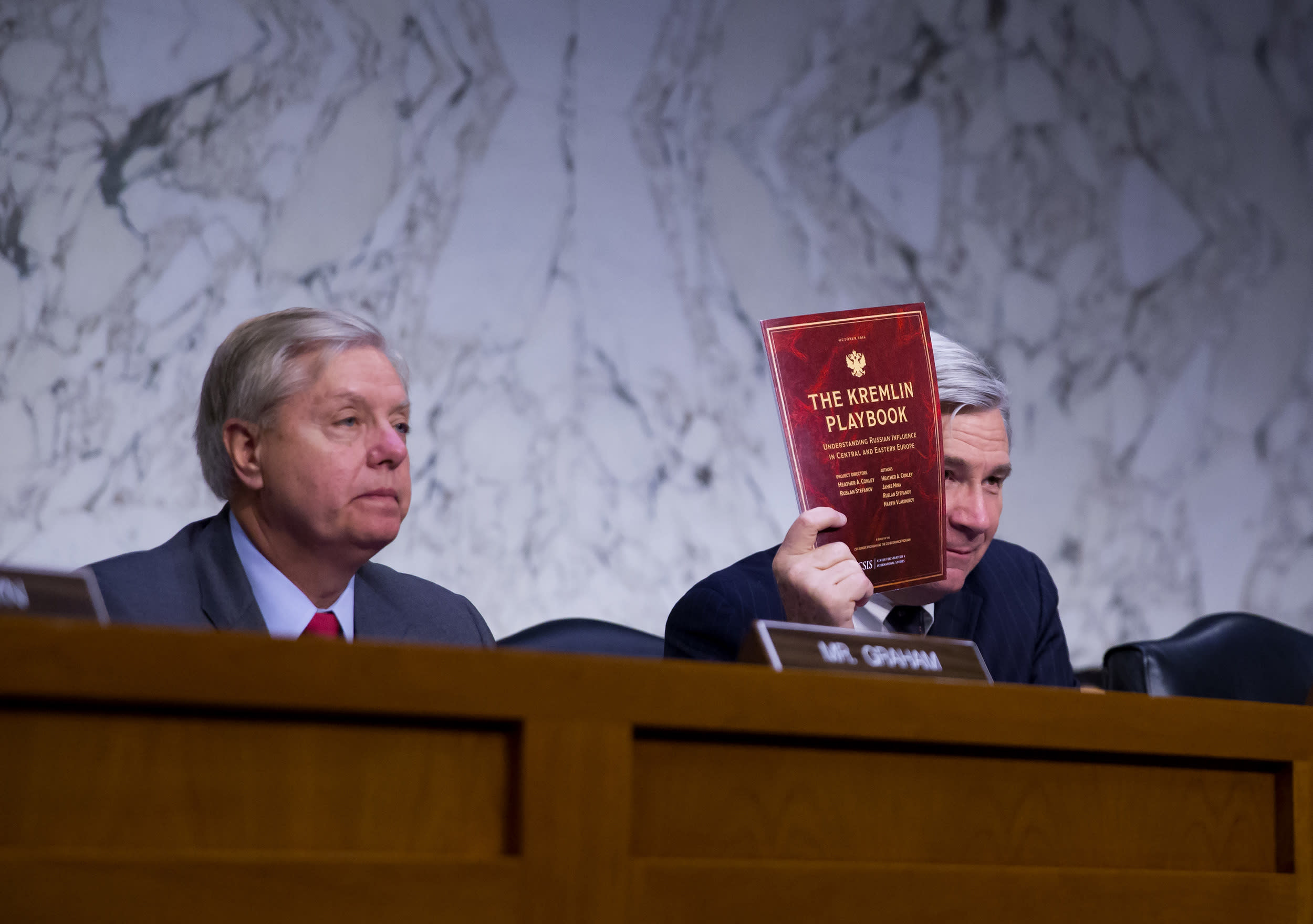 WASHINGTON, DC - MAY 8:  Sen. Sheldon Whitehouse (D-RI) holds up a copy of 'The Kremlin Playbook' as Sen. Lindsay Graham (R-SC) listens at a hearing of the Senate Judicary Committee's Subcommittee on Crime and Terrorism in the Hart Senate Office Building on Capitol Hill May 8, 2017 in Washington, DC. Before being fired by U.S. President Donald Trump, Yates testified that she had warned the White House about contacts between former National Security Advisor Michael Flynn and Russia that might make him vulnerable to blackmail. (Photo by Eric Thayer/Getty Images)