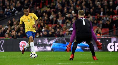 El delantero brasileño Gabriel Jesus enfrenta al arquero de la selección de fútbol de Inglaterra Joe Hart
