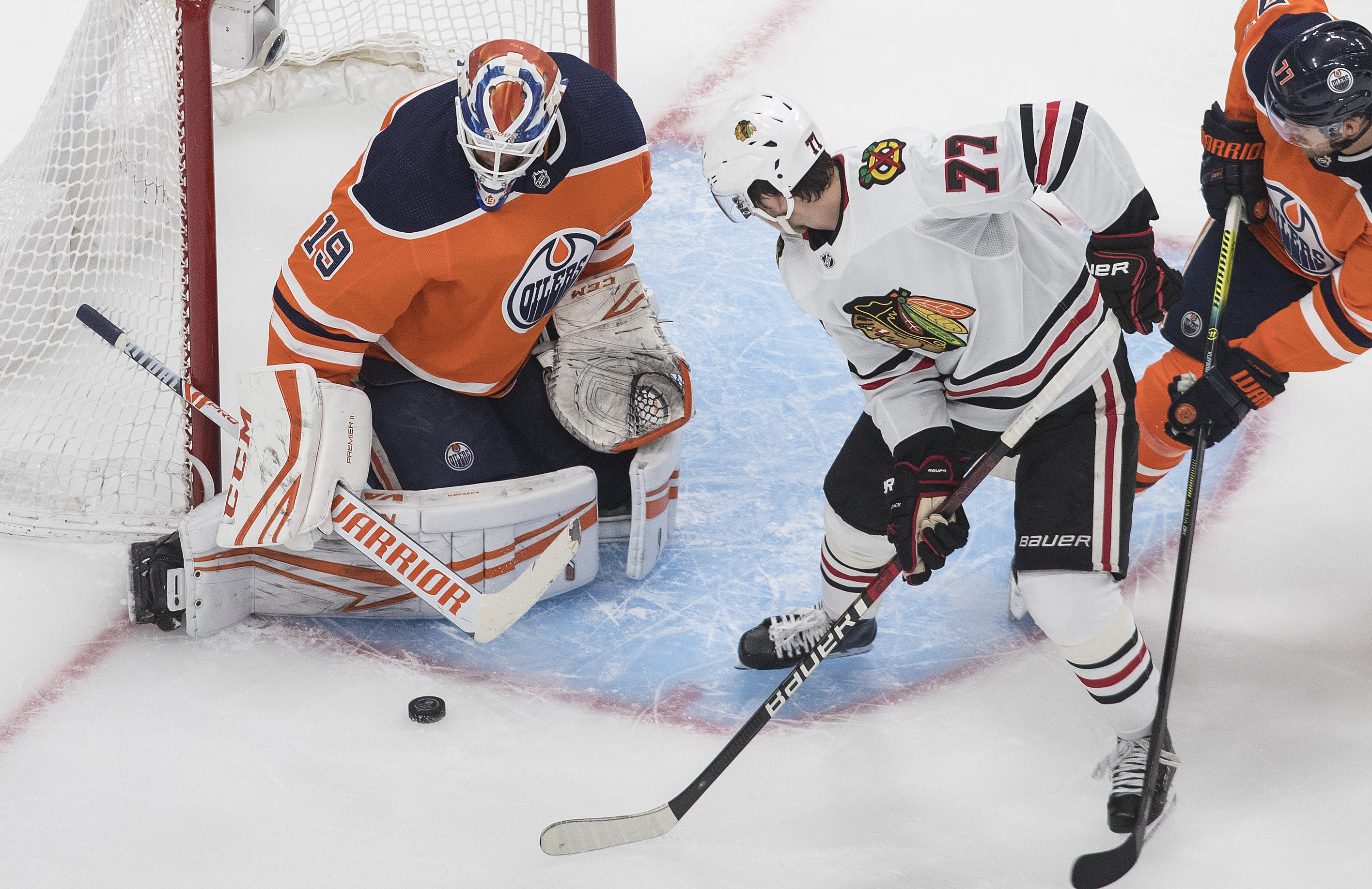 Edmonton Oilers goalie Mikko Koskinen (19) makes the save against Chicago Blackhawks' Kirby Dach (77) during second-period NHL hockey Stanley Cup playoff game action in Edmonton, Alberta, Saturday, Aug. 1, 2020. (Jason Franson/The Canadian Press via AP)