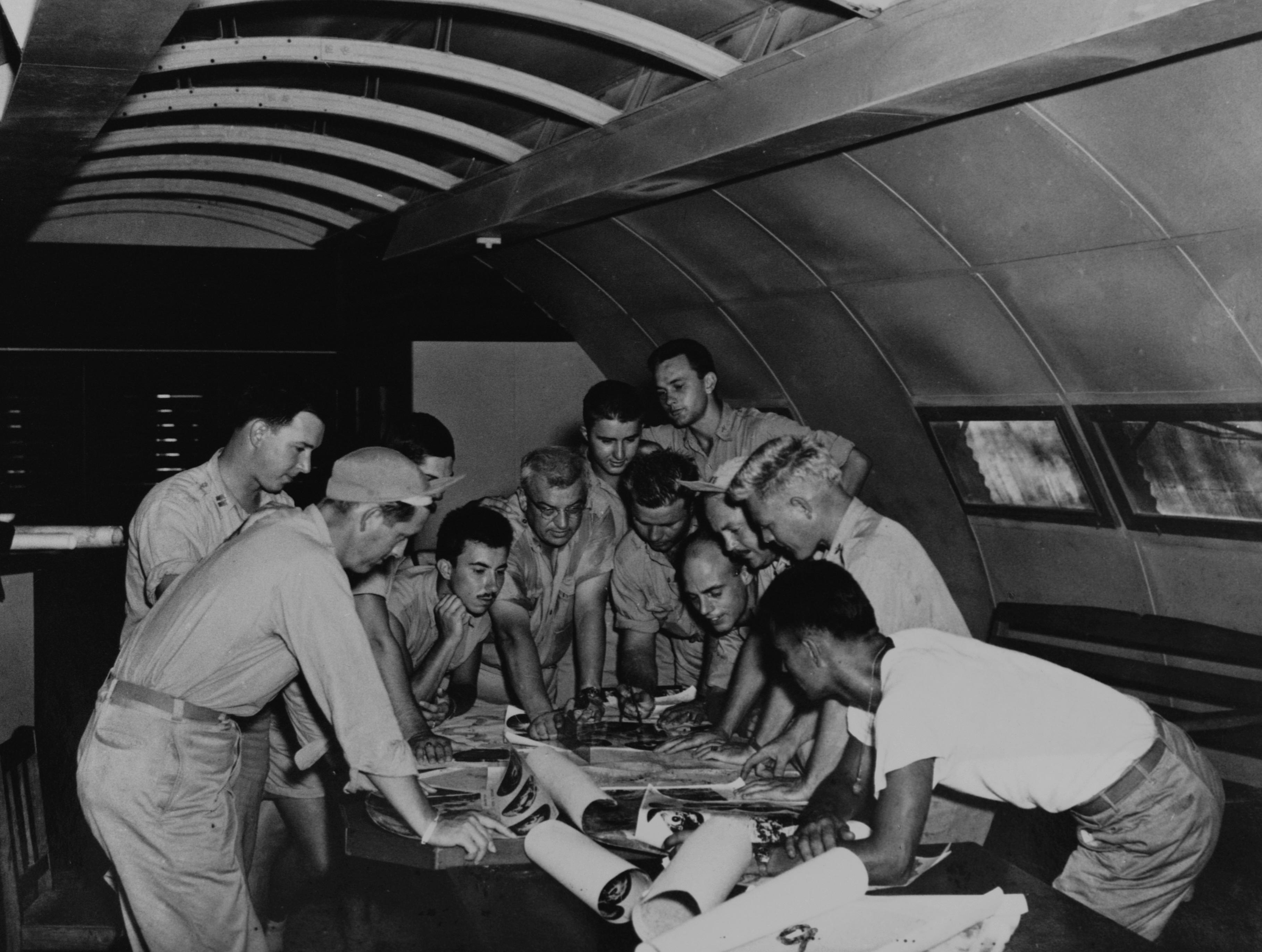 <p>The flight crews of two planes go over planes for the dropping of the first atomic bombs. The middle-aged man in the center is Lt. Col. Payette. On the left, in the foreground in profile is Lt. Ralph Devore. The man looking over Payette's shoulder is Major Chuck Sweeney. Sweeney commanded and Devore flew with the mission to drop the second bomb on Nagasaki. To the right in profile are Lts. Thomas Ferebee (in cap, with mustache) and Morris Jeppson, both of whom flew with the first mission to bomb Hiroshima. (Photo: Corbis via Getty Images) </p>