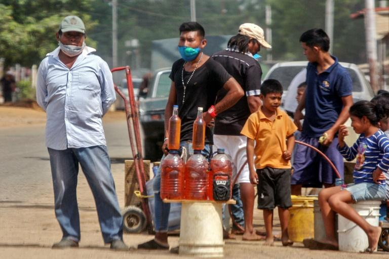 People offer gasoline for sale on the streets of Maracaibo, Venezuela in July 2020 (AFP Photo/Luis BRAVO)