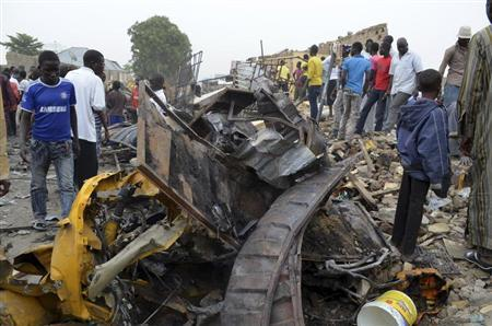 People look at damage in a market area after a bomb explosion in Ajilari-Gomari near the city's airport, Maiduguri