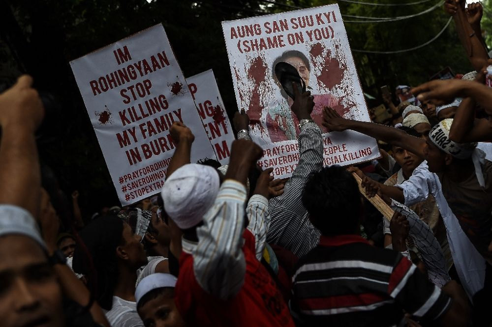 Ethnic Rohingya Muslim refugees hit a placard with a portrait of Myanmar State Counsellor and Foreign Minister Aung San Suu Kyi during a protest in Kuala Lumpur, Malaysia