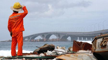 FILE PHOTO: A construction worker looks on as the China-funded Sinamale bridge is seen in Male, Maldives September 18, 2018. REUTERS/Ashwa Faheem/File Photo