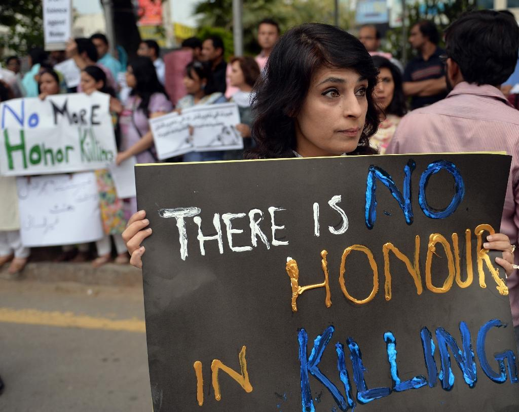 Pakistani human rights activists hold placards during a protest in Islamabad on May 29, 2014 against the killing of pregnant woman Farzana Parveen