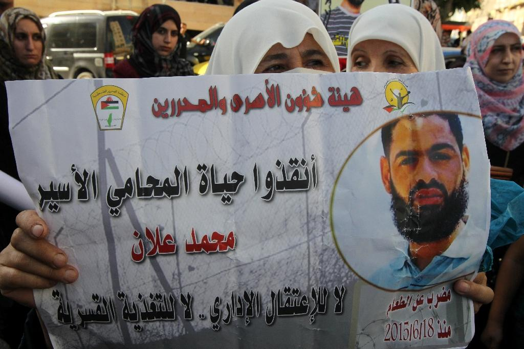 A Palestinian woman holds a poster depicting hunger striker Mohammed Allan, at a rally in support of Palestinian prisoners on August 17, 2015 in the West Bank city of Hebron (AFP Photo/Hazem Bader)