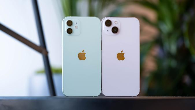 A green iPhone 12 and pink iPhone 13 with their backs facing the camera. You can see their dual cameras. On the left, the pair of sensors are stacked on top of each other. On the right, they're laid out diagonally. The module on the right is also slightly wider and taller, and the cameras themselves are slightly bigger.