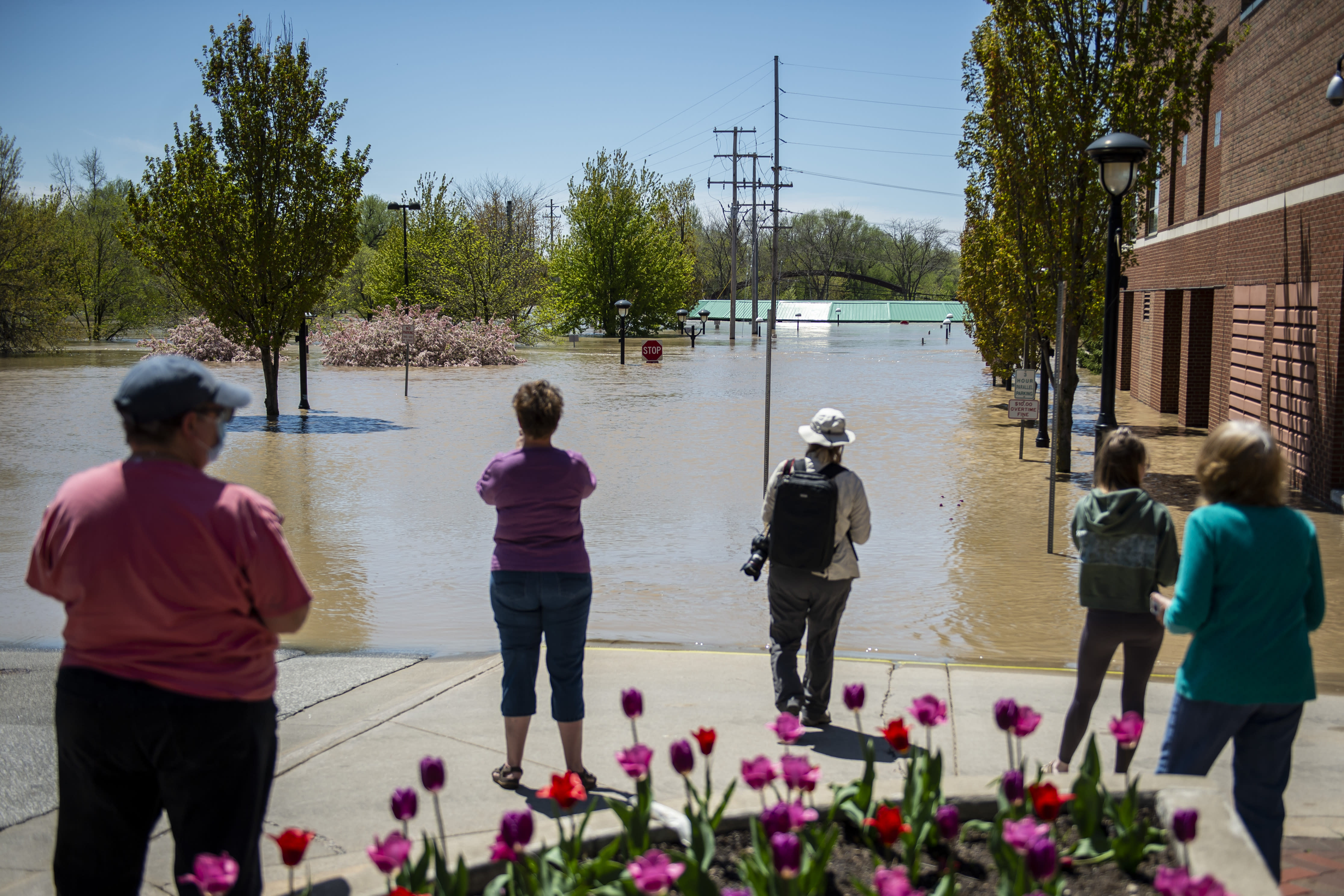 People check out the flooding near the H Hotel in downtown Midland, Mich., on Wednesday, May 20, 2020. After the Edenville Dam failed and the Tittabawassee River flooded surrounding areas, many residents were urged to leave their homes. (Kaytie Boomer/The Bay City Times via AP)