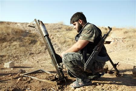 A Free Syrian Army fighter sets up a homemade rocket to be launched towards forces loyal to Syria's President Bashar al-Assad based in the Kwers military airport in Aleppo