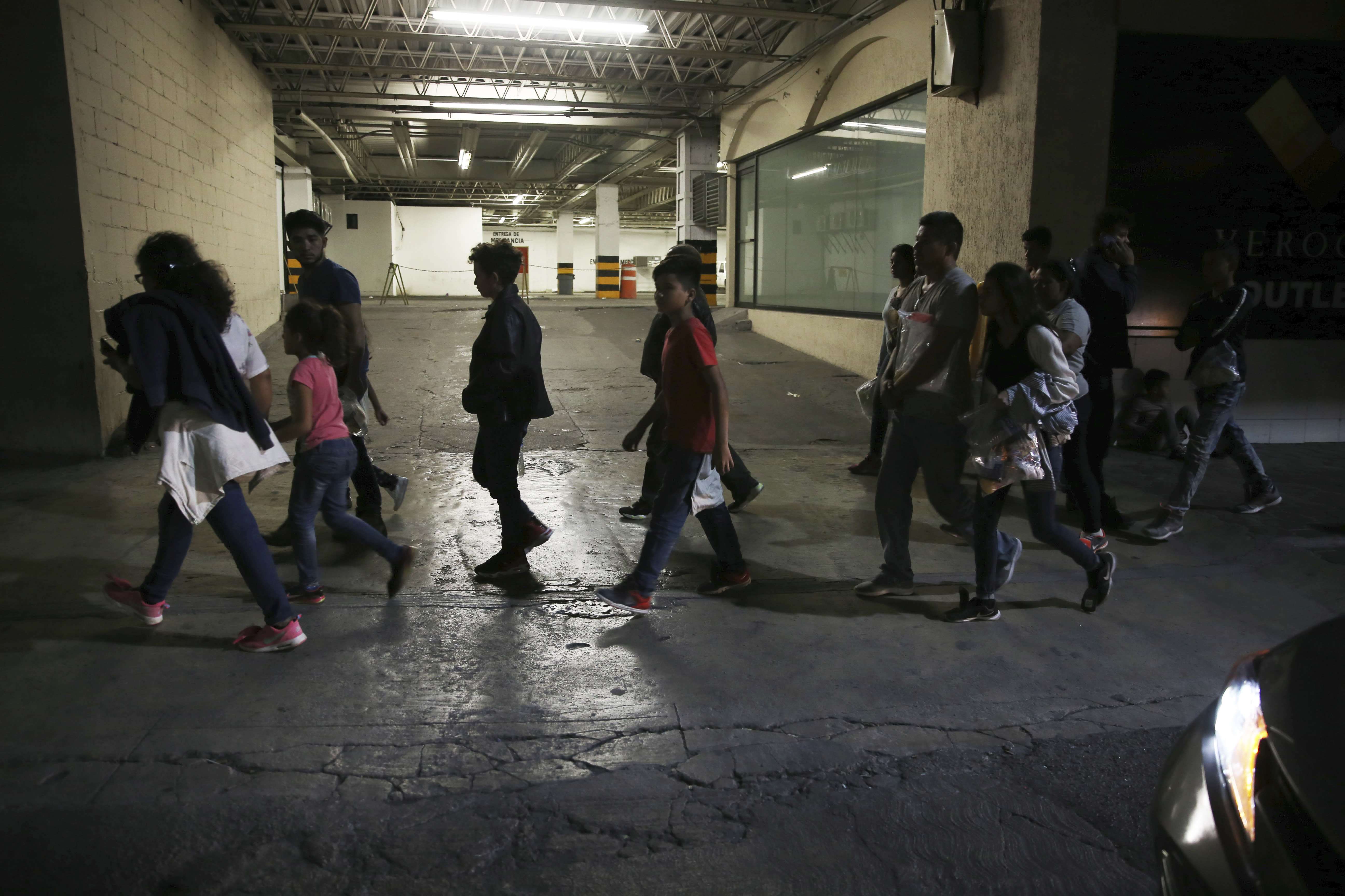 In this July 18, 2019 photo, migrants who have just been bused by Mexican Authorities from Nuevo Laredo to Monterrey, walk off the bus into the street in Monterrey, Mexico. All those taken to Monterrey who spoke with AP said that they had not asked for asylum in the US and some asked to be returned to their home countries, but were told that going to Mexico or remaining in detention were the only options. (AP Photo/Marco Ugarte)