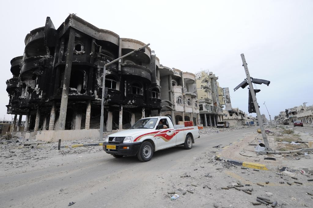 File photo shows Libyans driving through a destroyed neighbourhood in Sirte (AFP Photo/Philippe Desmazes)