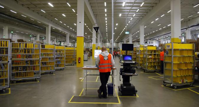 """A worker stands his designated workspace at a packing station as he supervises items for delivery from the 70,000 square metre warehouse floor at Amazon's new distribution center in Brieselang, near Berlin November 28, 2013. Germany's antitrust watchdog has dropped an investigation into  Amazon after the world's biggest Internet retailer agreed to stop forcing third-party merchants to offer their cheapest price when selling products on its platform. Andreas Mundt, the president of the German cartel office, said it had decided to set aside the case against Amazon after the company agreed to cancel that demand from the terms and conditions of its contracts with merchants. """"Making pricing demands to your own competitors cannot be justified in any circumstances, not even with the undeniable advantages of an online market place.""""  REUTERS/Tobias Schwarz (GERMANY - Tags: BUSINESS)"""
