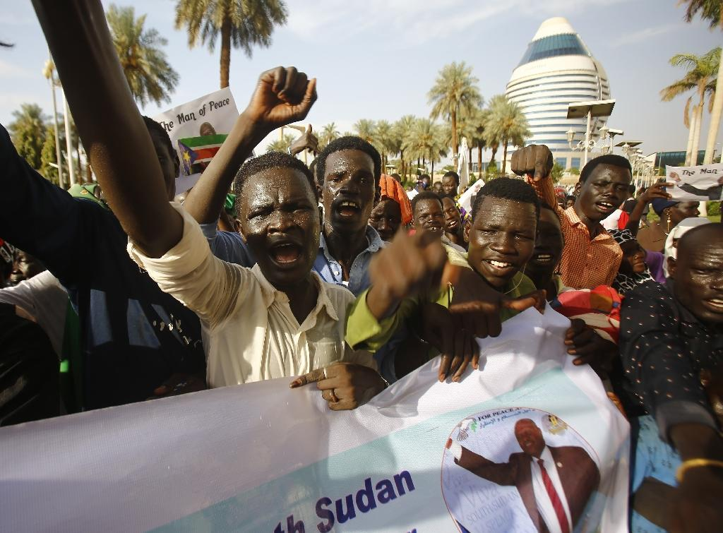People celebrate a new power-sharing deal between rivals intended to bring peace to South Sudan, where tens of thousands have died in civil war. (AFP Photo/ASHRAF SHAZLY)