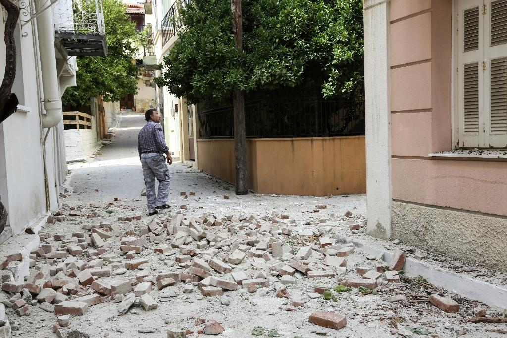 A man walks through a damaged street in the village of Plomari on the Greek island of Lesbos on June 12, 2017 (AFP Photo/)