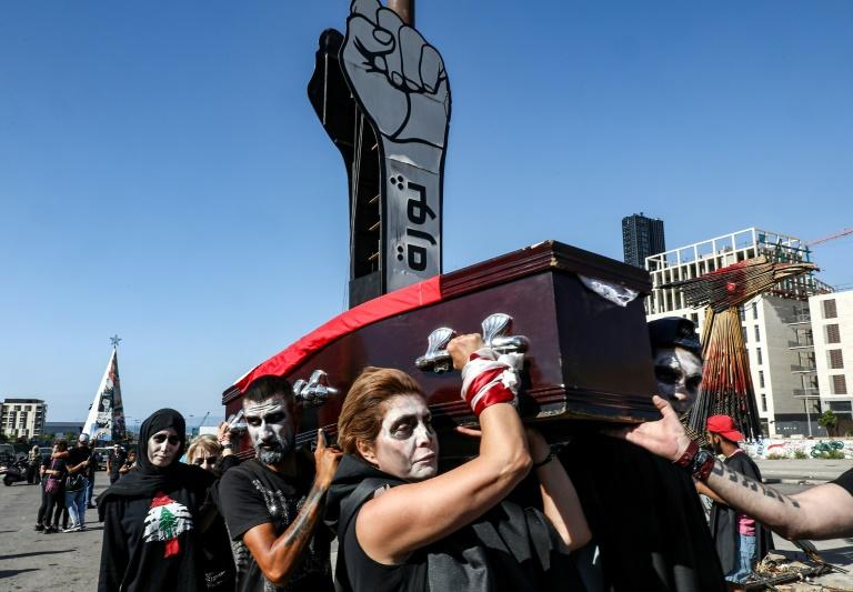 In this file photo taken on June 13, 2020, Lebanese anti-government protesters in Beirut take part in a symbolic funeral for the country amid a deepening economic crisis (AFP Photo/ANWAR AMRO)