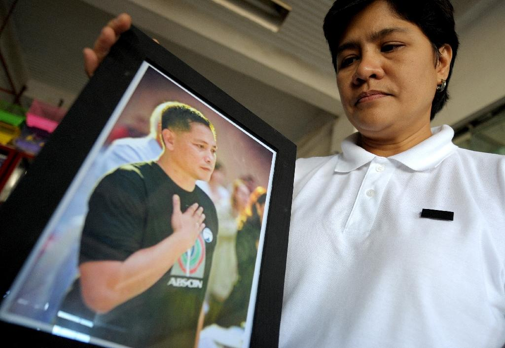Patricia Ortega, wife of slain Philippine environment activist Gerry Ortega, poses with a picture of her husband in Palawan's capital Puerto Princesa in 2011 (AFP Photo/Noel Celis)