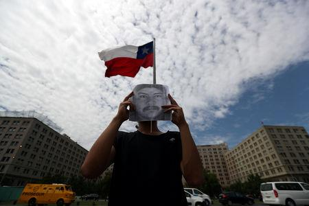FILE PHOTO: A demonstrator holds up an image of Camilo Catrillanca, an indigenous Mapuche man who was shot in the head during a police operation in 'Ercilla' town south of Santiago, outside the government house in Santiago, Chile, November 22, 2018. REUTERS/Ivan Alvarado/File Photo
