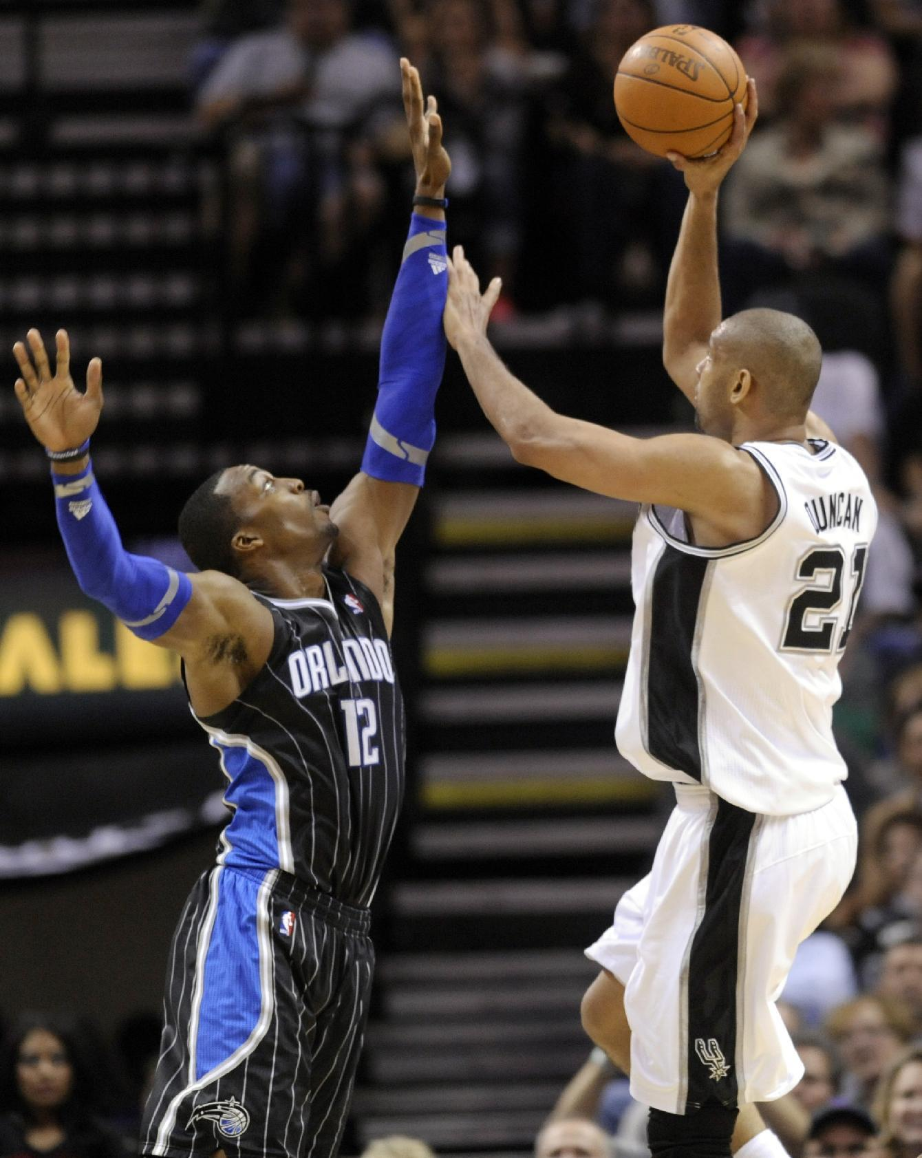 San Antonio Spurs forward Tim Duncan shoots over Orlando Magic center Dwight Howard during the second half of an NBA basketball game Wednesday, March 14, 2012, in San Antonio. The Spurs won 122-111. (AP Photo/Bahram Mark Sobhani)
