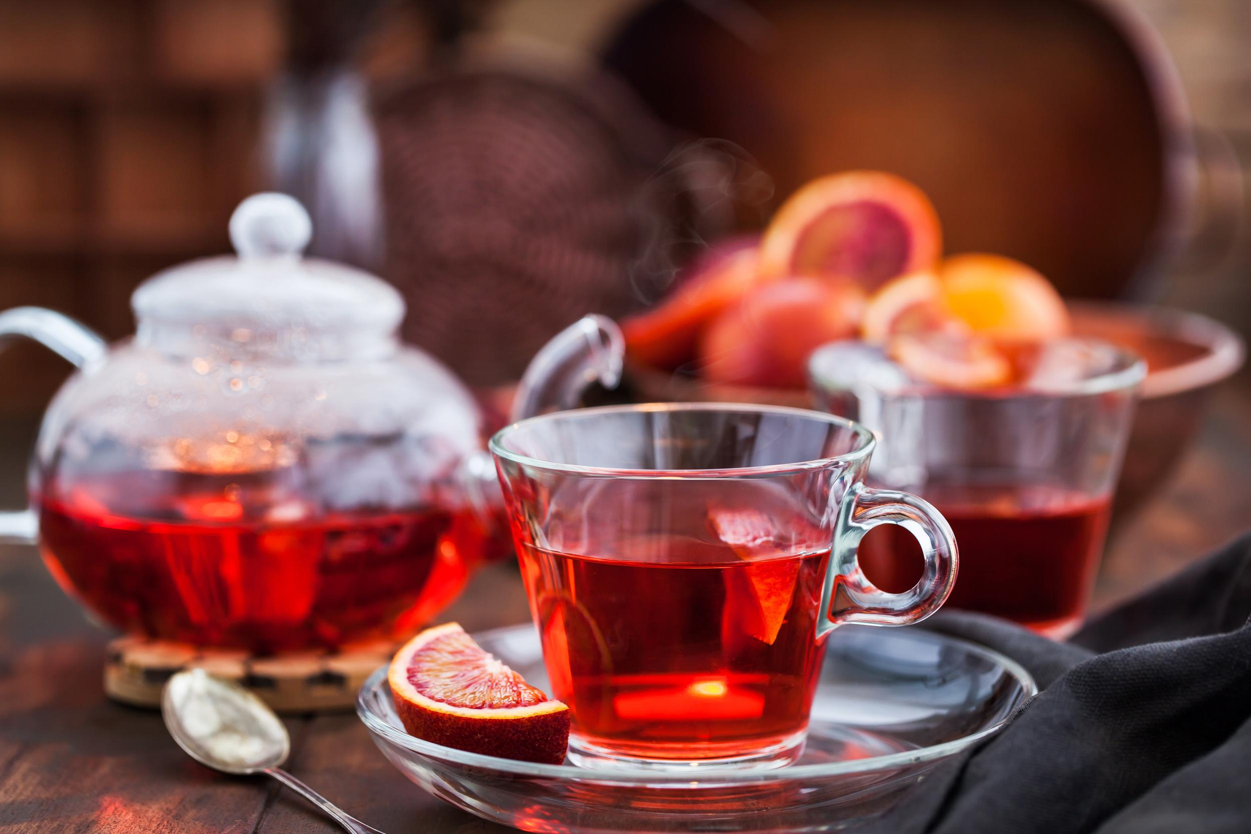 Red hot hibiscus tea in glass mug and teapot on wooden table