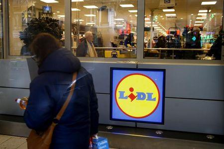 A woman walks past a logo inside a store of discount supermarket chain Lidl in Paris