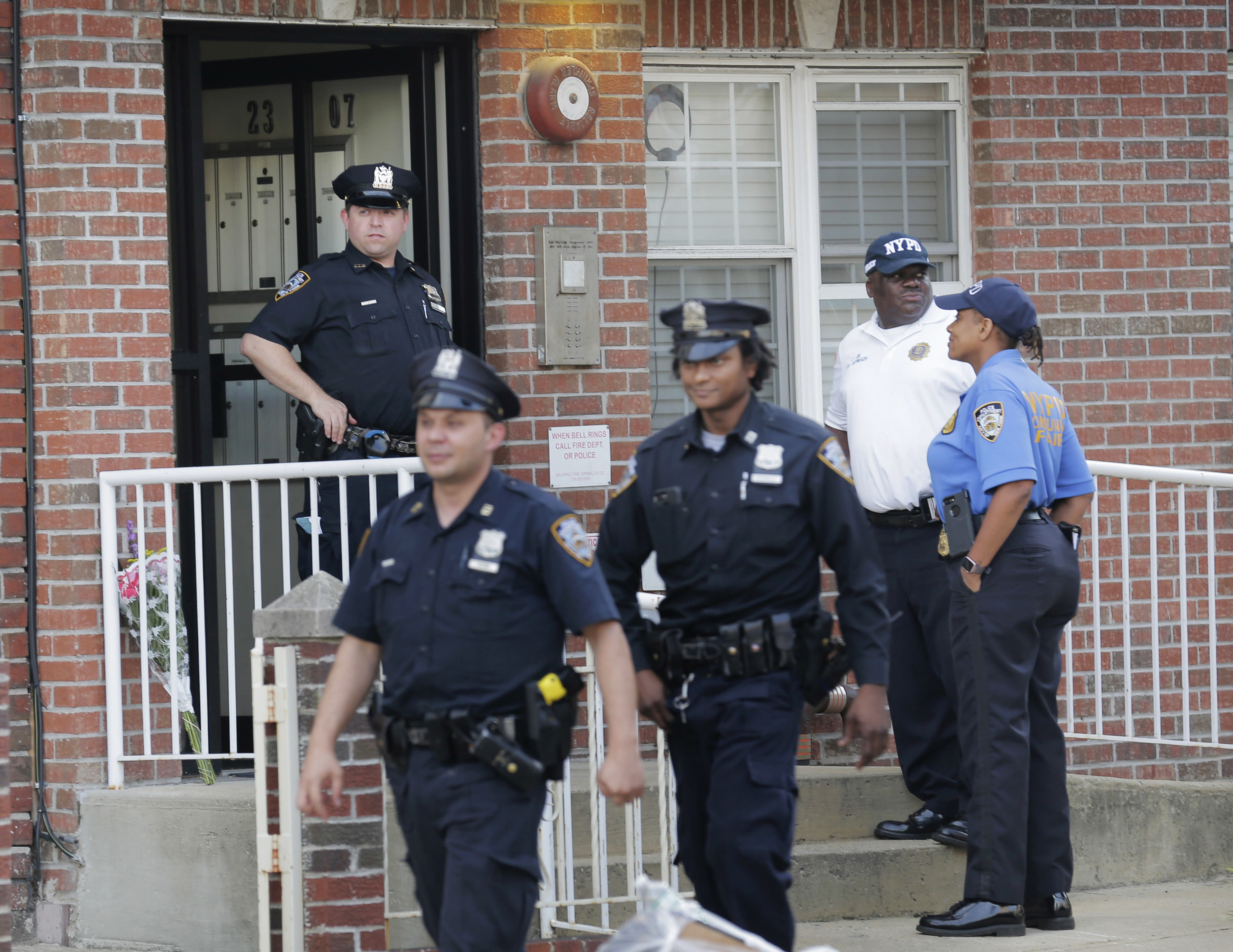 Police officers stand in front of a building where there was a shooting with multiple fatalities in the Queens borough of New York, Tuesday, July 31, 2018. (AP Photo/Seth Wenig)