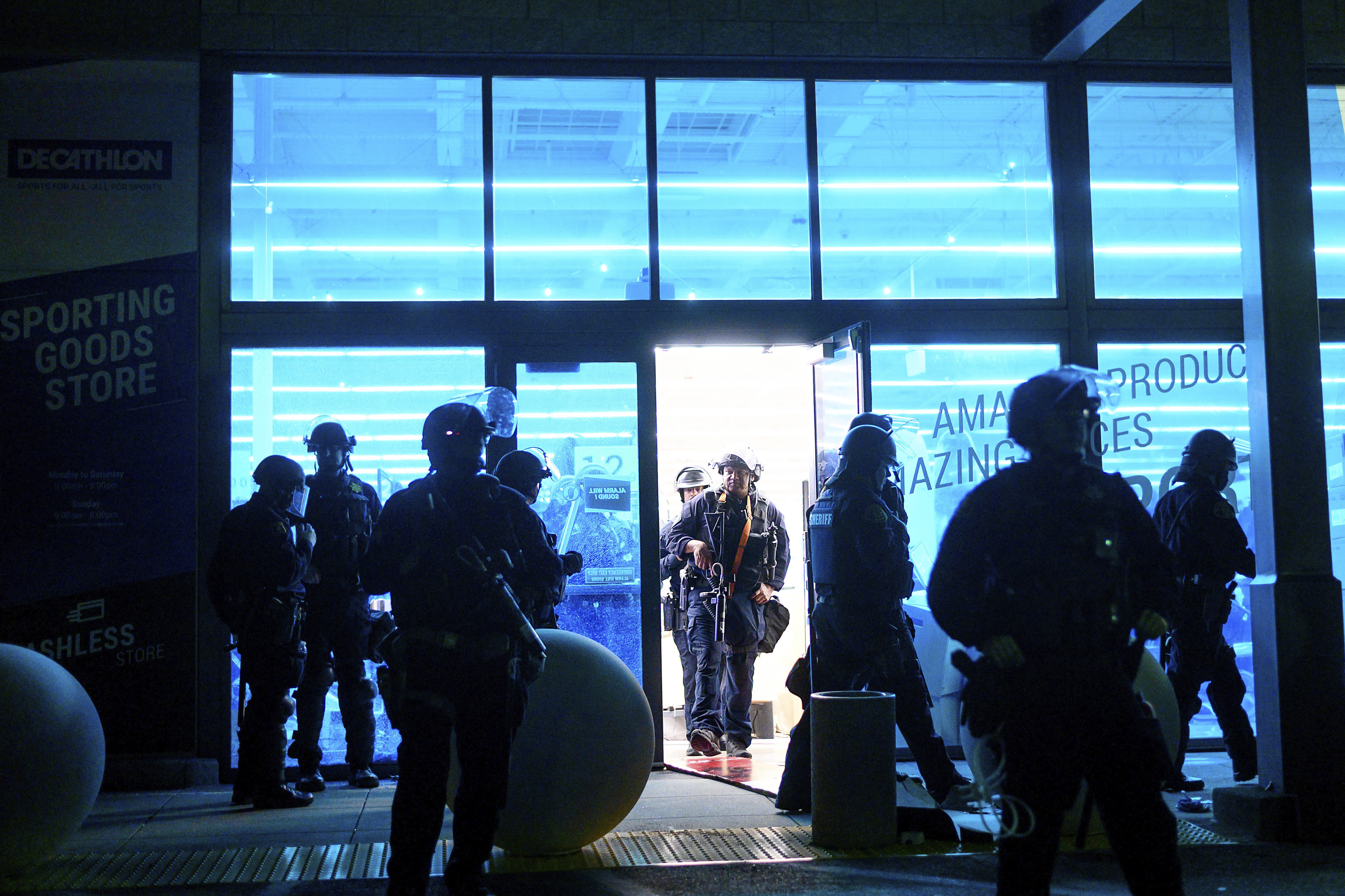 FILE - In this May 30, 2020, file photo, police officers leave a vandalized Decathlon sporting goods store in Emeryville, Calif. Police say many of the smash-and-grab thefts have been carried out by caravans of well-coordinated criminals that have coincided with or followed protests over the death of George Floyd, who was killed by a Minneapolis police officer who pressed his knee into Floyd's neck. (AP Photo/Noah Berger, File)
