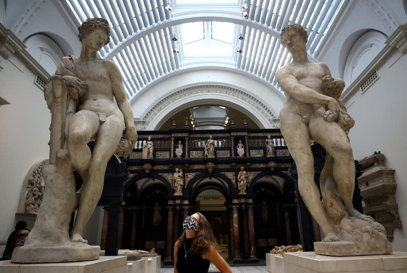 A Victoria & Albert (V&A) Museum gallery assistant poses for members of the media in front of the Apollo and Zephyr sculptures by Pietro Francavilla during preparations to reopen the museum, in London