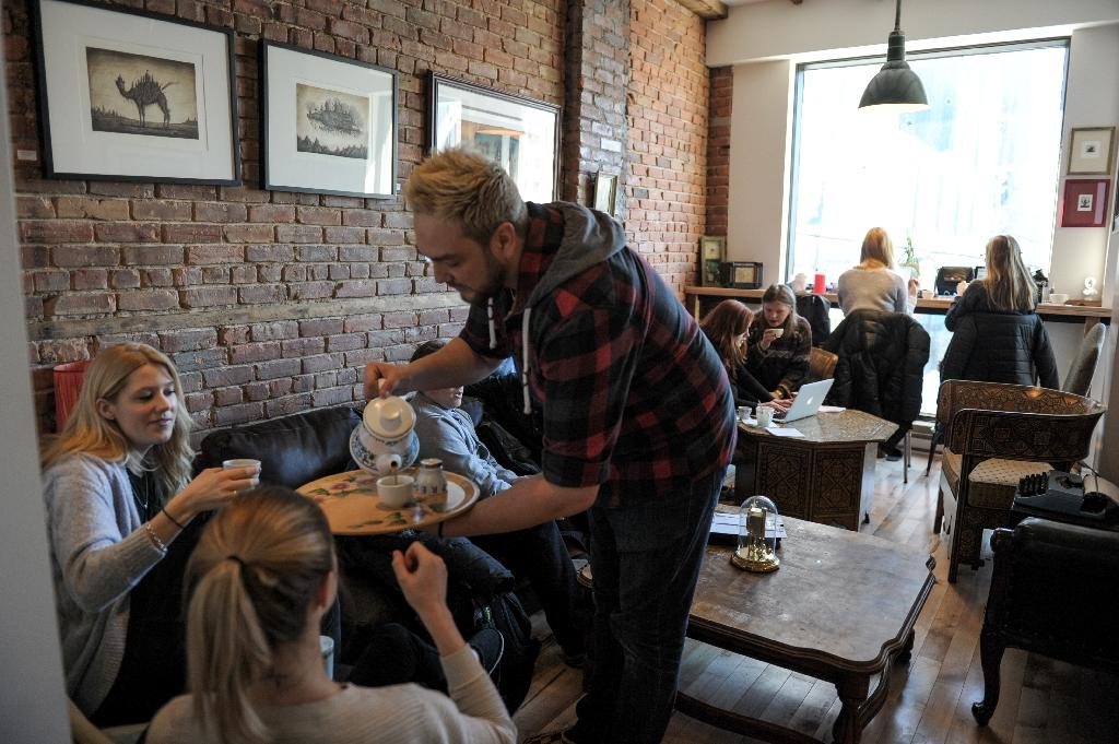 David Chevrier, manager of the Anticafe in downtown Montreal, serves tea to costumers (AFP Photo/Alice Chiche)