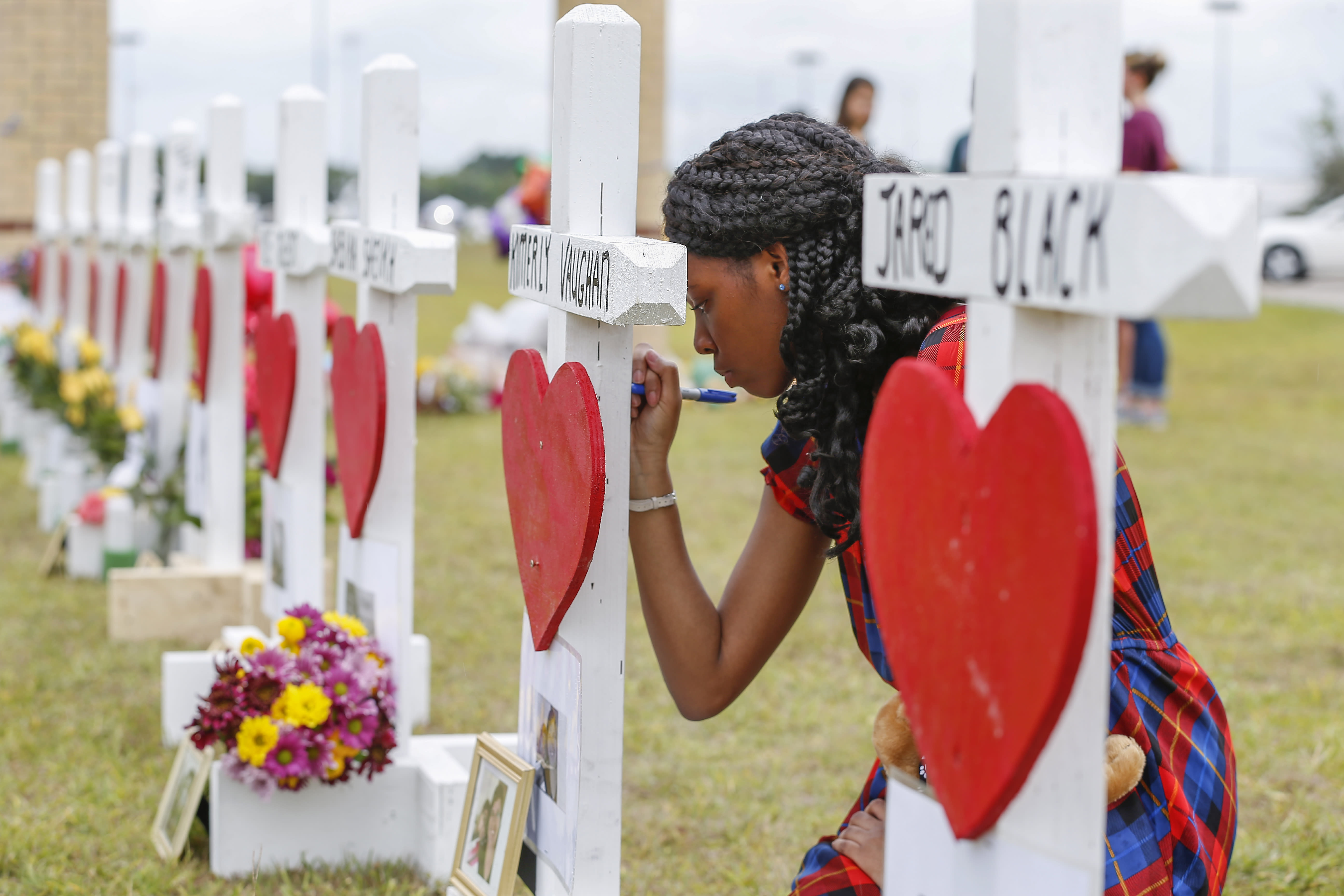 <p>Santa Fe High School freshman, Jai Gillard writes messages on each of the 10 crosses in front the school Monday, May 21, 2018, in Santa Fe. Gillard, was in the art class Friday morning, knew all of the victims of the shooting. Texas Governor Greg Abbott has called for a moment of silence at 10 a.m. and came to the school to participate. (Photo: Steve Gonzales/Houston Chronicle via AP) </p>