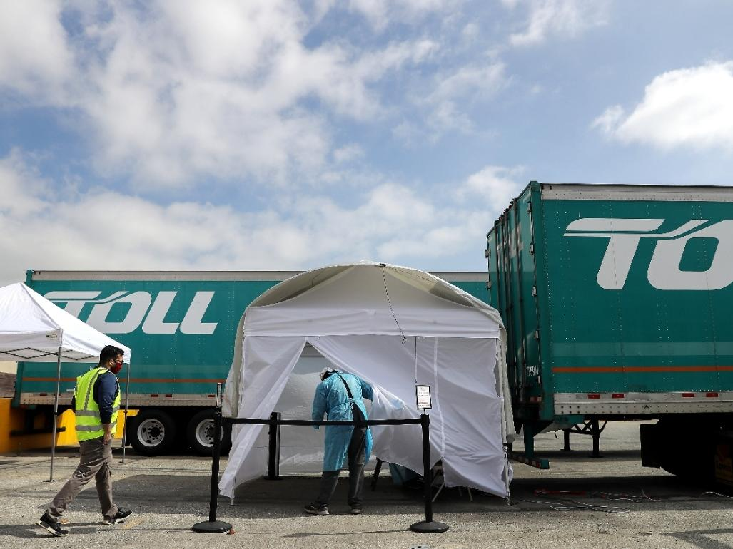 A worker (left) walks toward a tent to be tested for COVID-19 on Thursday at a testing site provided by the International Brotherhood of Teamsters in Long Beach, California.