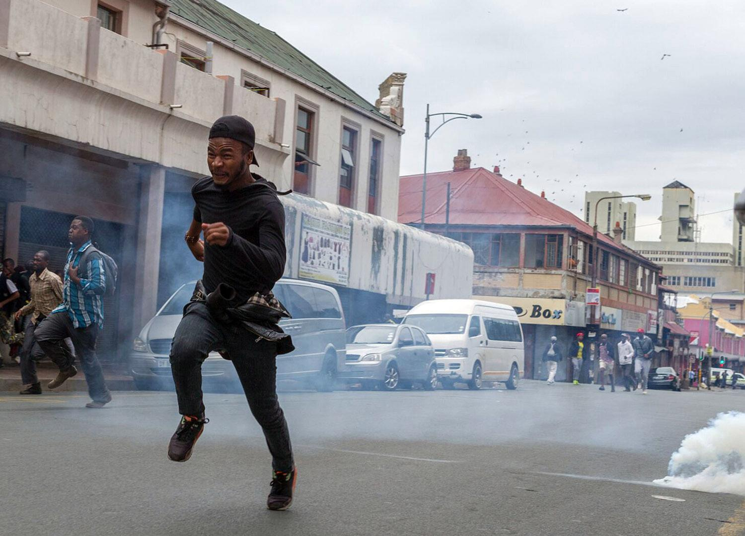 <p>Members of the ANC Youth League flee from teargas and rubber bullets being fired by police, at the end of a march by the main opposition Democratic Alliance party in Johannesburg, April 7, 2017. Thousands of South Africans demonstrated in major cities against President Jacob Zuma. Zuma's dismissal of the finance minister has fueled concerns over government corruption and a struggling economy. (Photo: Yeshiel Panchia/AP) </p>