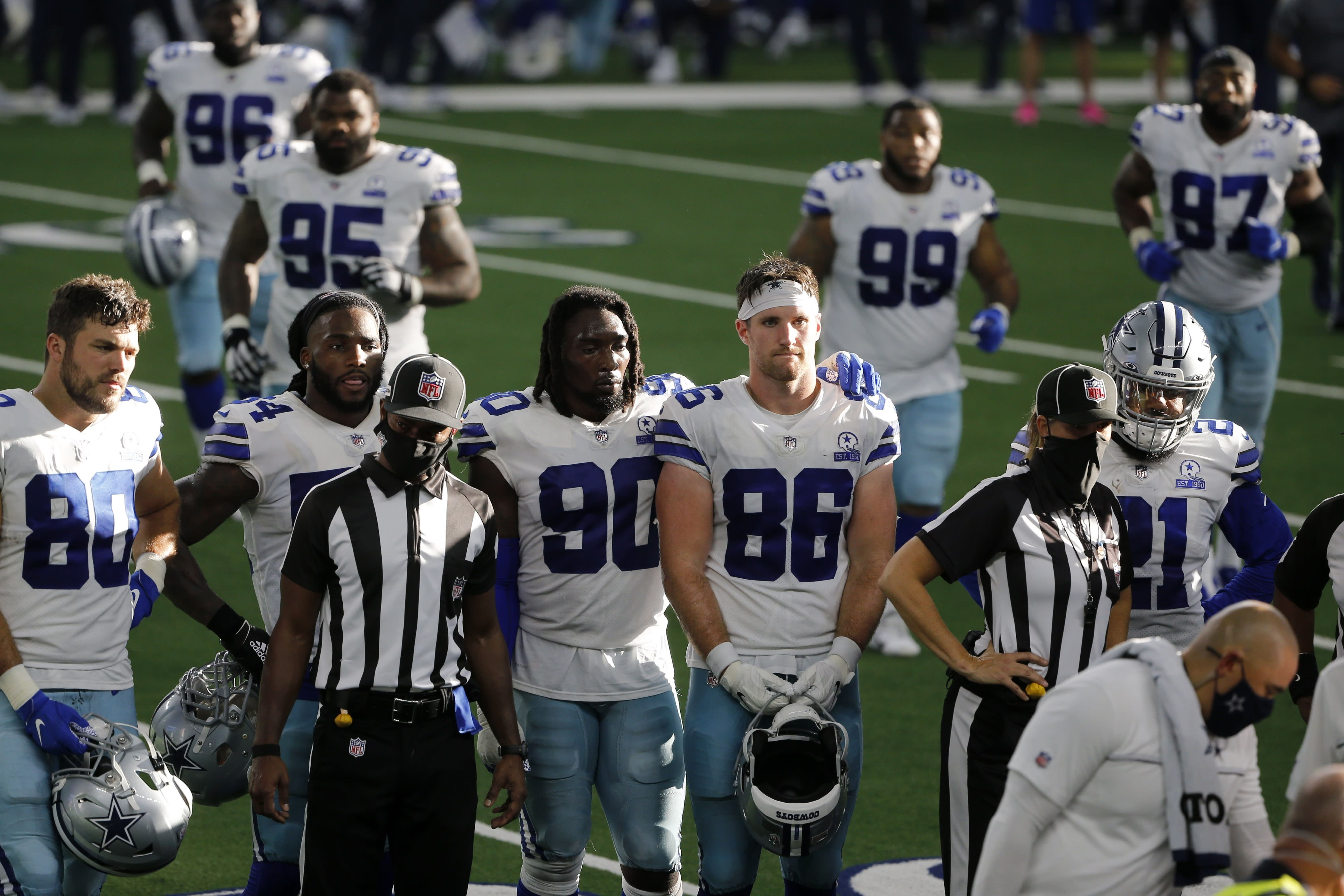 Dallas Cowboys players, Blake Bell (80), DeMarcus Lawrence (90), Dalton Schultz (86), Ezekiel Elliott (21) and others look on as quarterback Dak Prescott, not shown, receives medical attention after suffering a lower right leg injury running the ball against the New York Giants in the second half of an NFL football game in Arlington, Texas, Sunday, Oct. 11, 2020. (AP Photo/Michael Ainsworth)