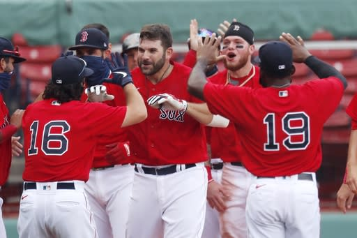 Boston Red Sox's Mitch Moreland, center, celebrates his two-run, walk-off home run during the ninth inning of a baseball game against the Toronto Blue Jays, Sunday, Aug. 9, 2020, in Boston. (AP Photo/Michael Dwyer)