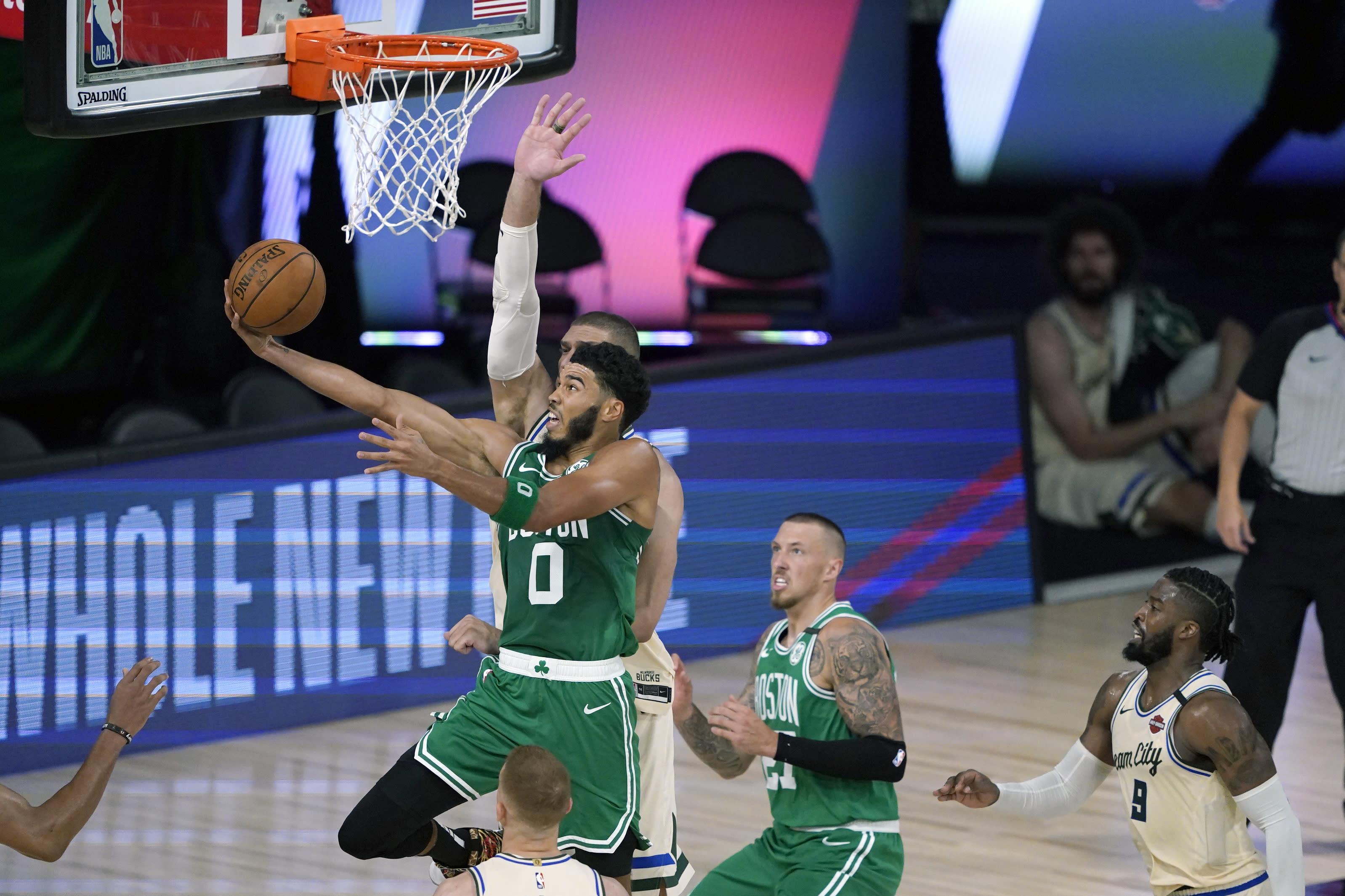 Boston Celtics' Jayson Tatum (0) heads to the basket during the first half of an NBA basketball game against the Milwaukee Bucks Friday, July 31, 2020, in Lake Buena Vista, Fla. (AP Photo/Ashley Landis, Pool)