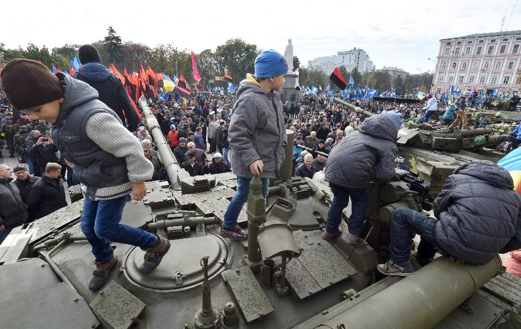 Children play on a tank during a military exhibition to mark Defender's Day in Kiev on October 14, 2015 (AFP Photo/Genya Savilov)