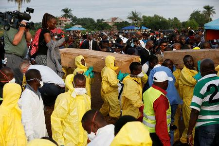 Heelth workers carry the remains of victims of the mudslide for burial at the Paloko cemetery, in Waterloo, Sierra Leone