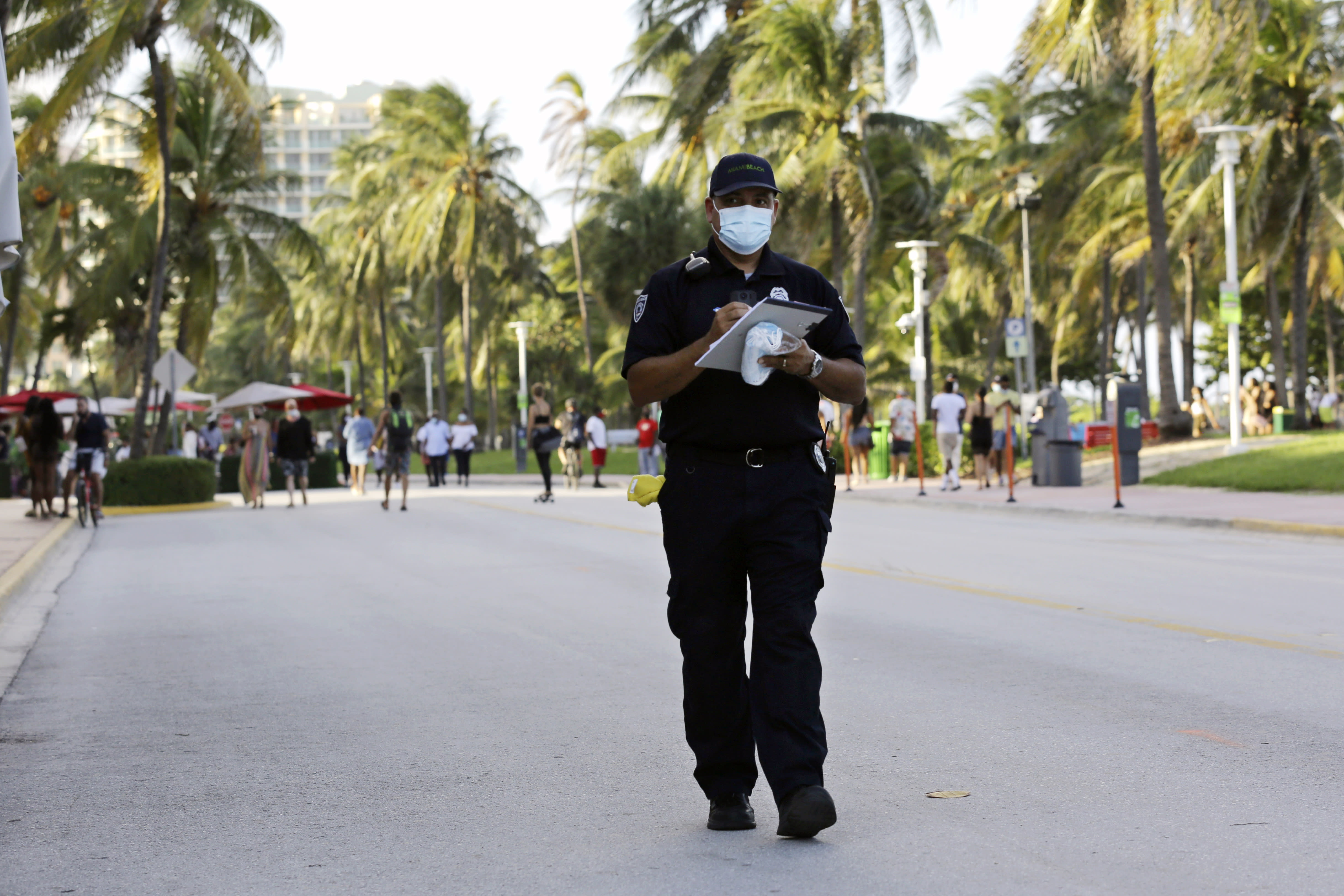 Luis Negron, a Miami Beach code compliance officer, walks along Ocean Drive amid the coronavirus pandemic, Friday, July 24, 2020, in Miami Beach, Fla. Masks are mandated both indoors and outdoors in Miami Beach. People found not wearing a mask are subject to a civil fine of $50. (AP Photo/Lynne Sladky)