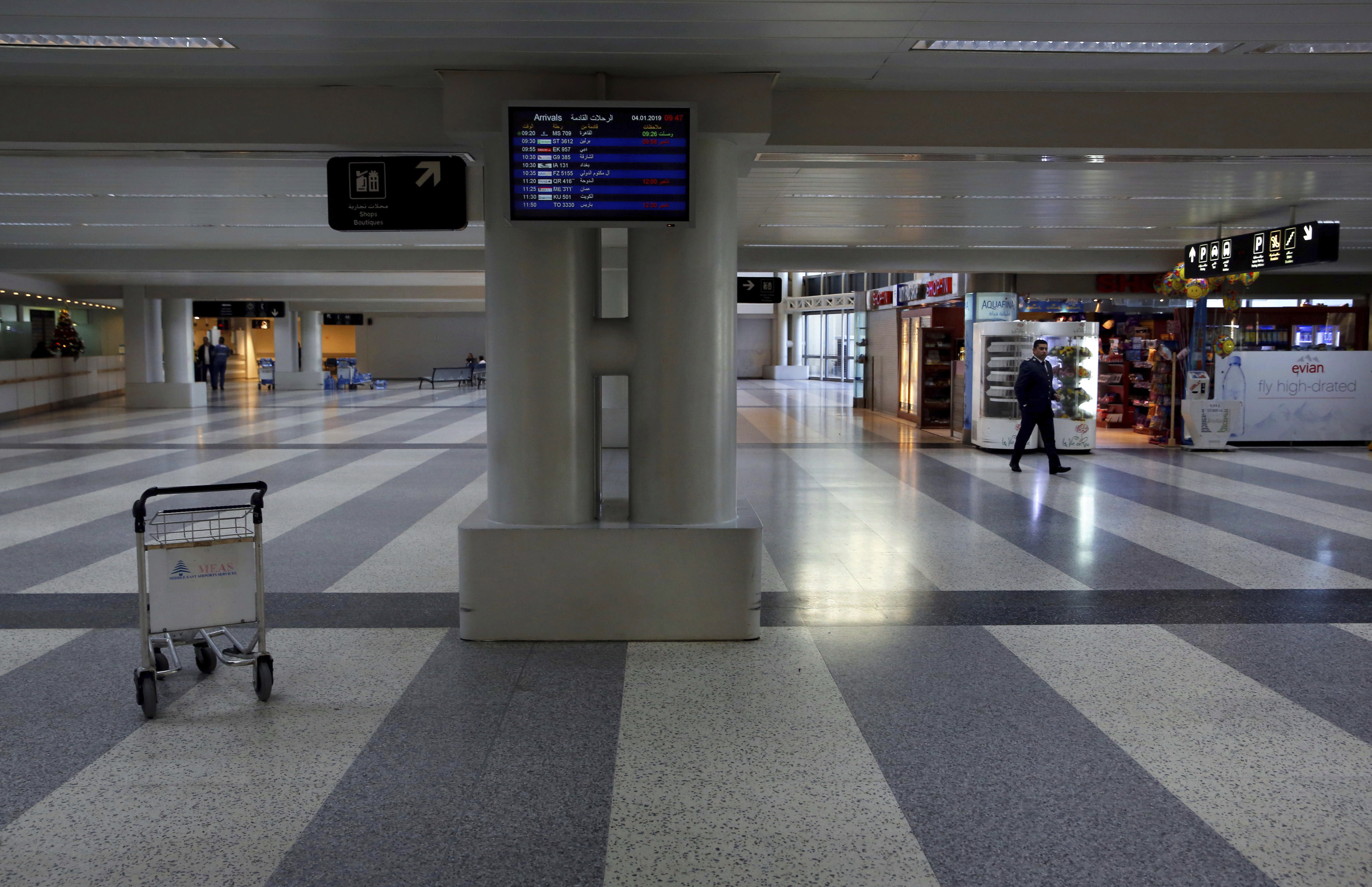 An officer walks through the almost empty arrival hall of the Rafik Hariri International Airport during a strike in Beirut, Lebanon, Friday, Jan. 4, 2019. Parts of Lebanon's public and private sectors have gone into a strike called for by the country's labor unions to protest worsening economic conditions and months of delays in the formation of a new government. (AP Photo/Bilal Hussein)