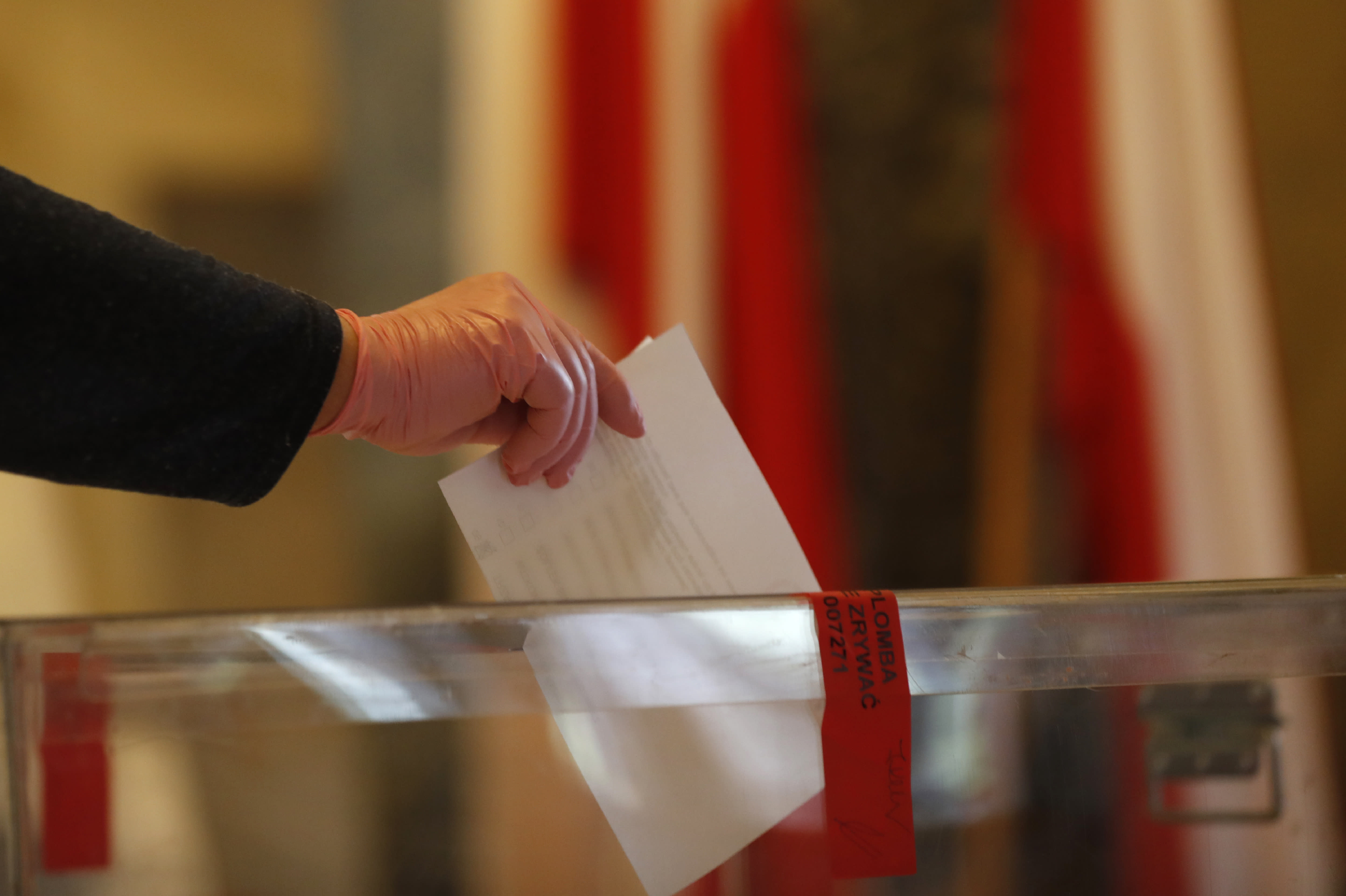 A resident, wearing protective gloves, casts a vote during presidential election in Warsaw, Poland, Sunday, June 28, 2020. The election will test the popularity of incumbent President Andrzej Duda who is seeking a second term and of the conservative ruling party that backs him. (AP Photo/Petr David Josek)