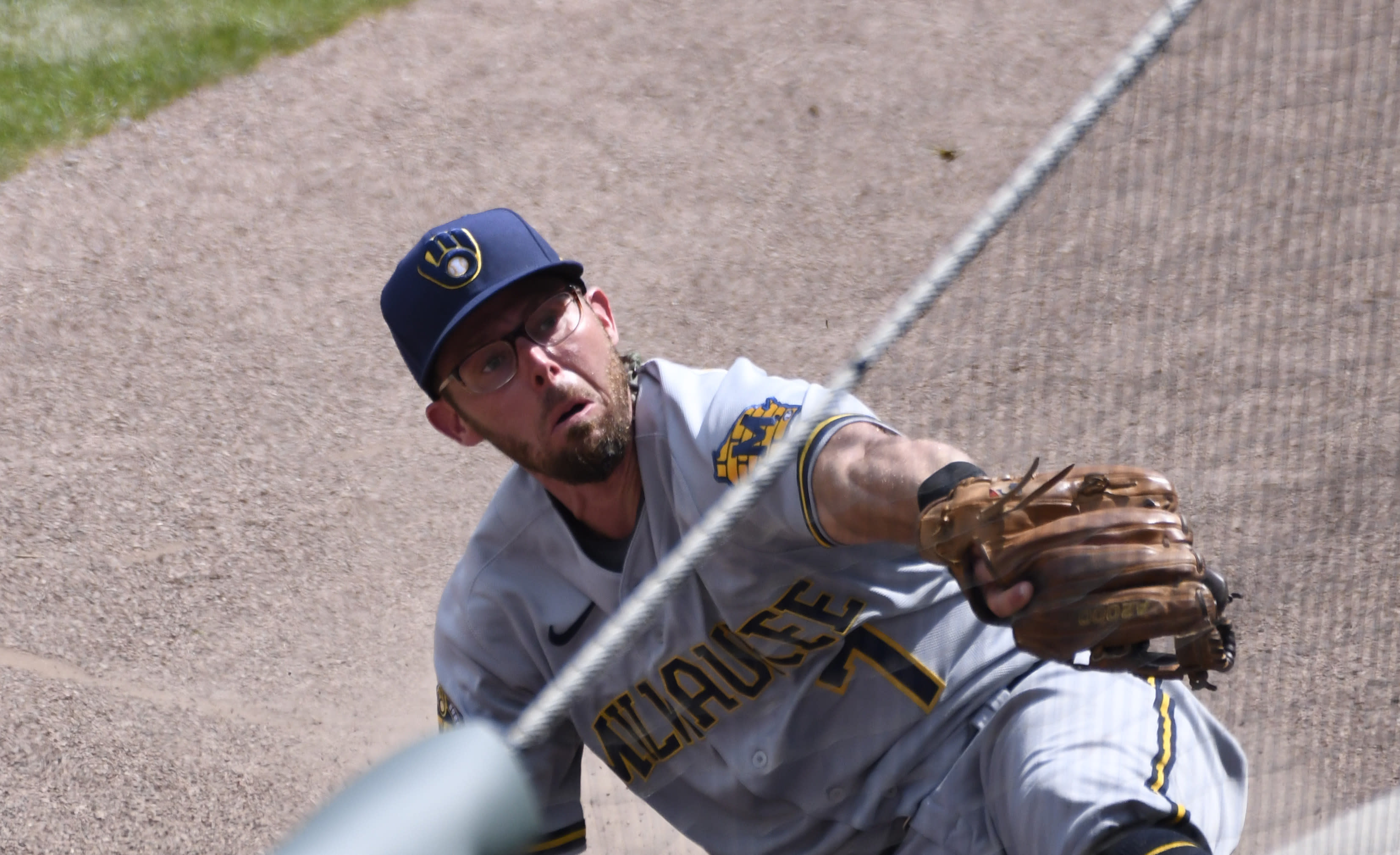 Milwaukee Brewers third baseman Eric Sogard tries to catch a foul ball hit by Chicago Cubs designated hitter Victor Caratini during the fourth inning of a baseball game Sunday, July, 26, 2020, in Chicago. (AP Photo/David Banks)