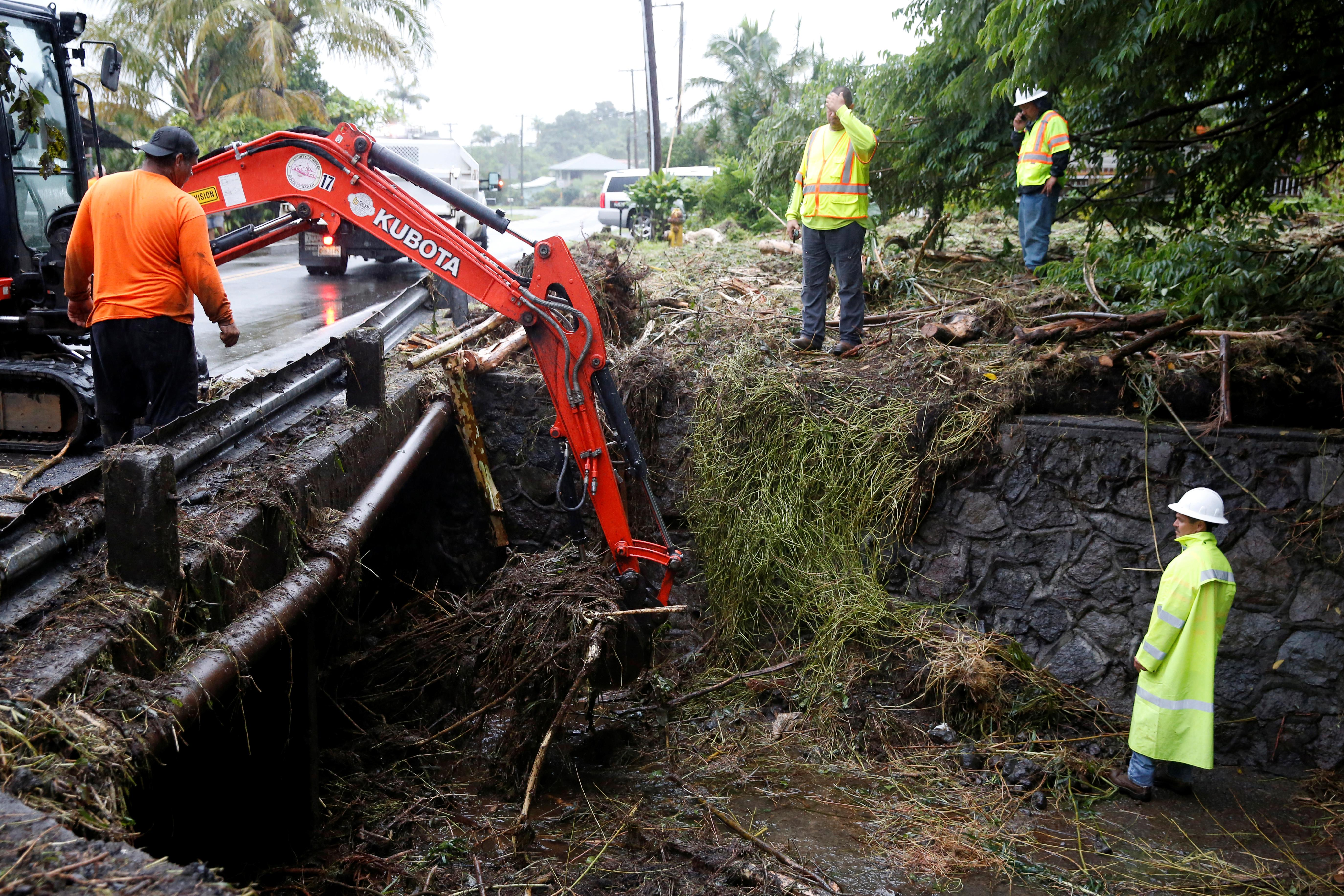 <p>Hawaii County employees clean up debris from flooding caused by Hurricane Lane in Hilo, Hawaii, Aug. 25, 2018. (Photo: Terray Sylvester/Reuters) </p>