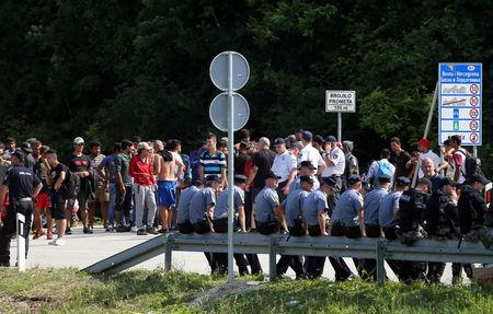FILE PHOTO: Migrants and Bosnian police eye one another in Velika Kladusa, Bosnia, near the border with Croatia