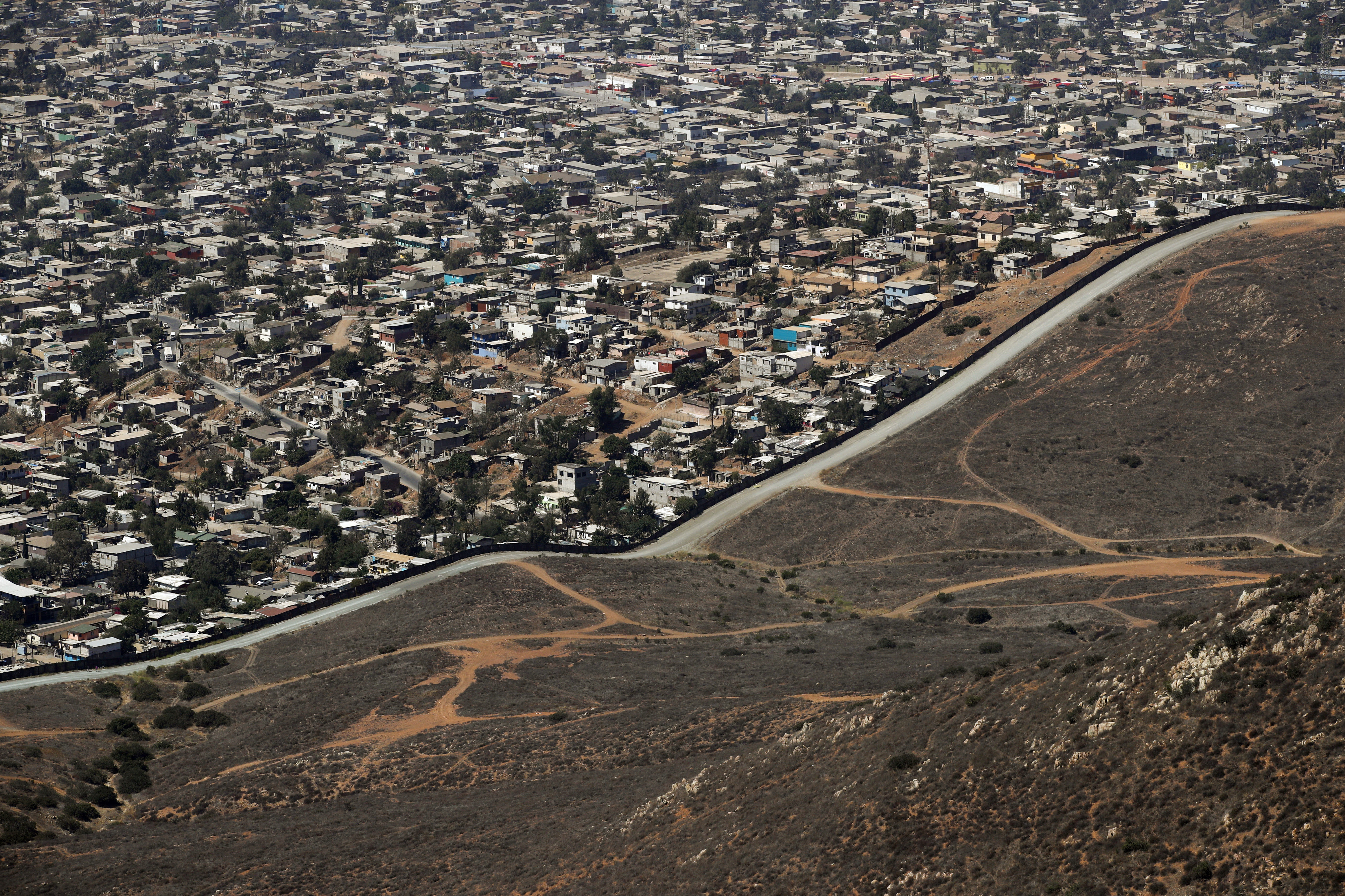 FILE - In this Thursday, June 28, 2018 file photo a road runs alongside a border wall that separates Tijuana, Mexico, top, from San Diego. The Tijuana and San Diego border crossing is the world's busiest land border crossing, but also now sees relatively few illegal crossings.(AP Photo/Jae C. Hong,File)