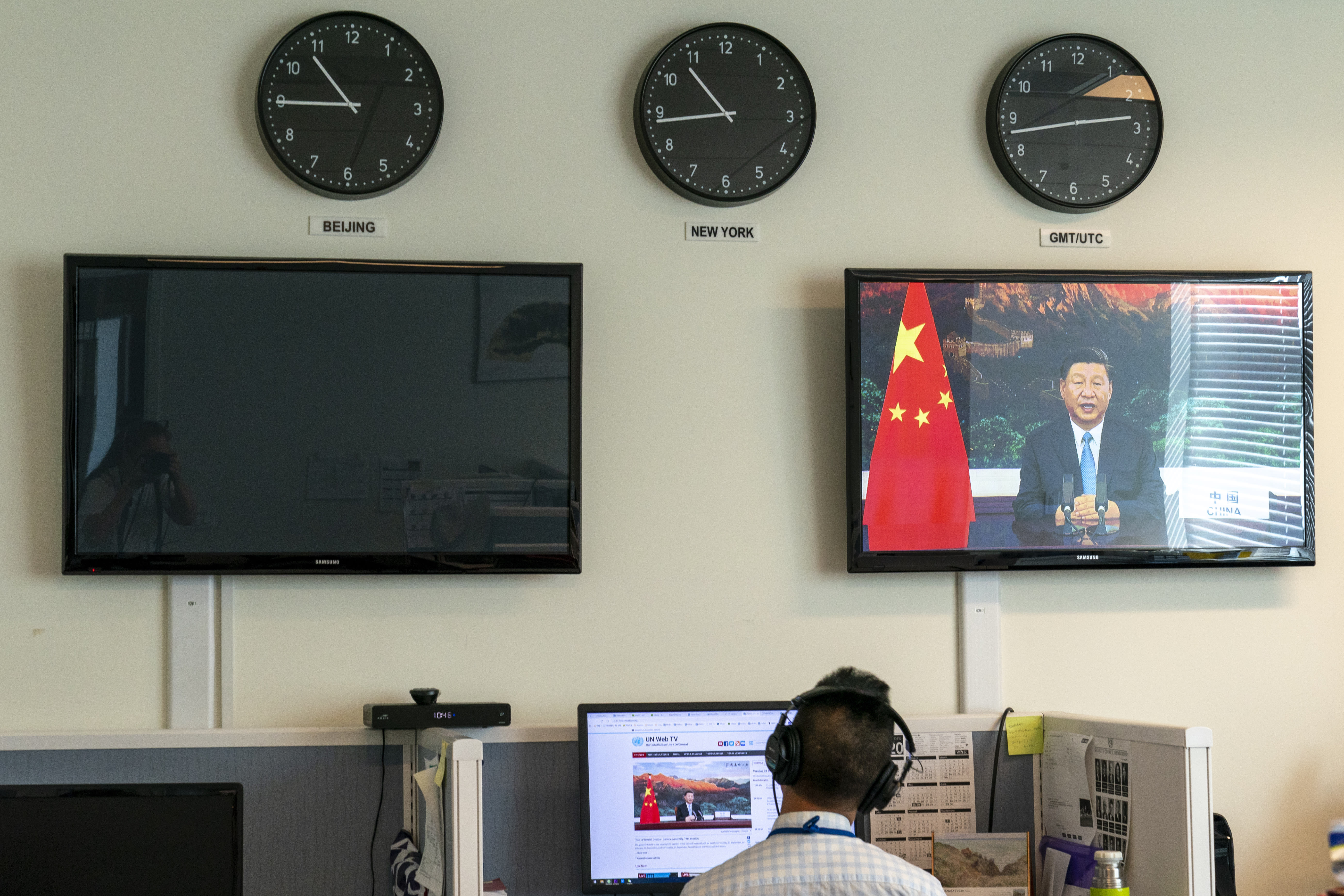 """A reporter with the Xinhua Press Agency watches as President Xi Jinping is seen on a video screen remotely addressing the 75th session of the United Nations General Assembly, Tuesday, Sept. 22, 2020, at U.N. headquarters. This year's annual gathering of world leaders at U.N. headquarters will be almost entirely """"virtual."""" Leaders have been asked to pre-record their speeches, which will be shown in the General Assembly chamber, where each of the 193 U.N. member nations are allowed to have one diplomat present. (AP Photo/Mary Altaffer)"""