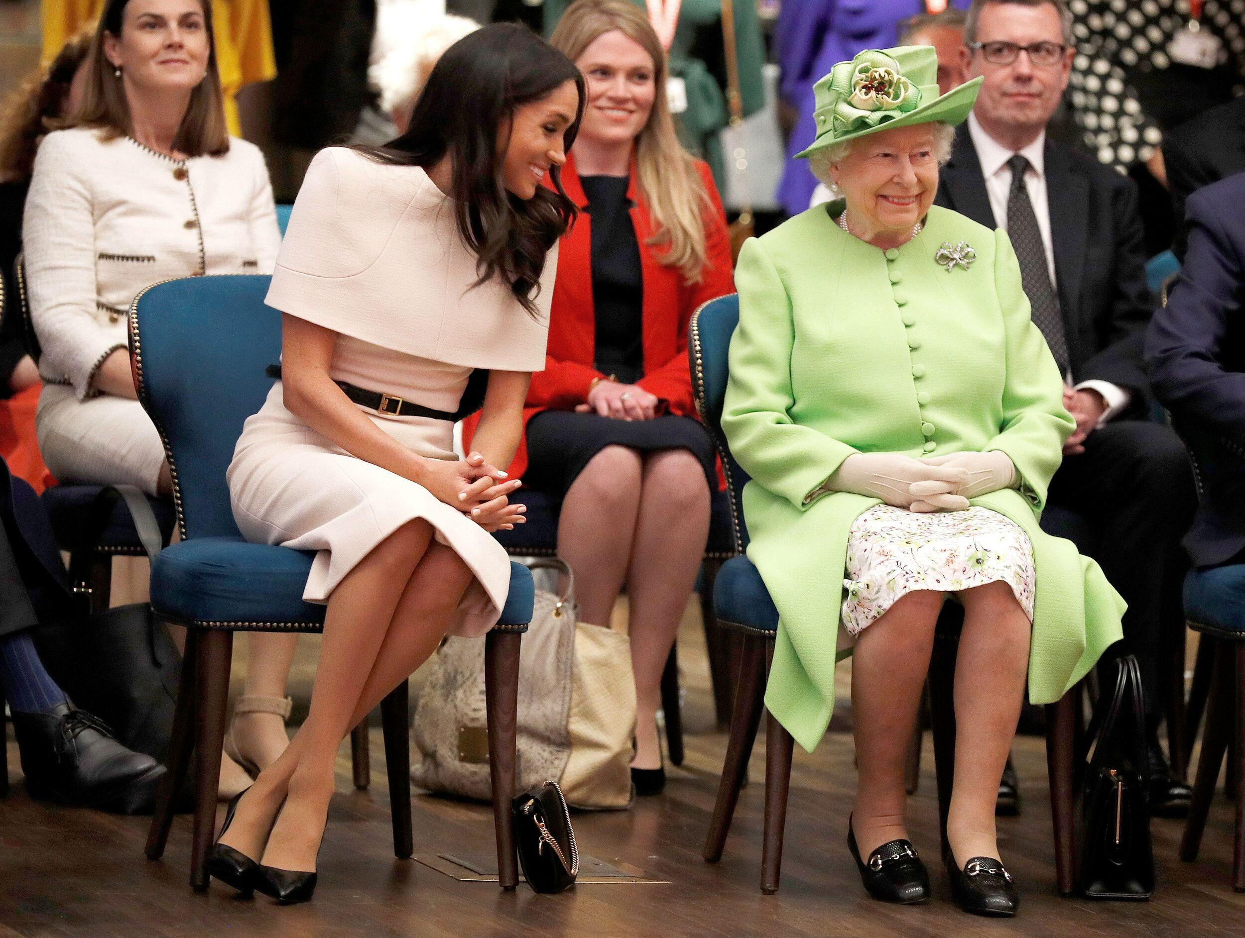 TOPSHOT - Britain's Queen Elizabeth II and Meghan, Duchess of Sussex gesture during their visit to the Storyhouse in Chester, Cheshire on June 14, 2018. (Photo by PHIL NOBLE / POOL / AFP)        (Photo credit should read PHIL NOBLE/AFP/Getty Images)